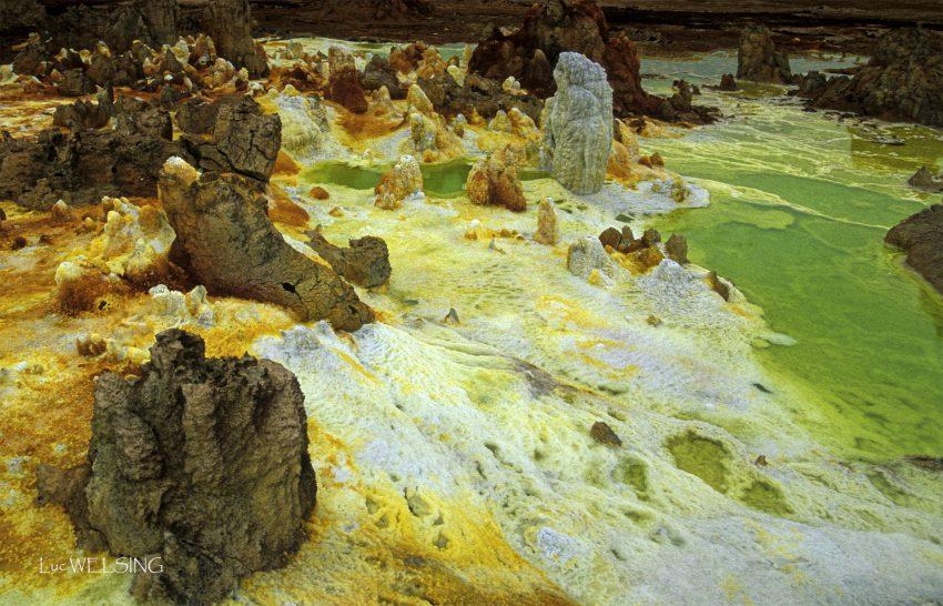 En constante mutation,  le site de Dallol,  propose ses fumerolles,  vapeurs soufrées ou non,  ses geysers et ses lagons verts.  Depuis les entrailles de la terre,  la vapeur d'eau,  se charge de minéraux,  et forme, tantôt des hornitos,  chaudières à dépôts,  tantôt de drôle de choses,  aux pétales écloses.  Ici, les dépôts frais forment des terrasses, Là, on évite les crevasses à potasse, Ailleurs, les couleurs s'assombrissent, Le temps que fument les évents, Le temps que passe le temps, Blanc, jaune, rouge puis brun. Comme un parfum. Comme une esquisse. site géothermique du Dallol, Dépression du Danankil, N 14°24 E 40°30 Ethiopie